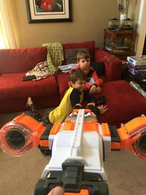 Kids playing with nerf gun on couch