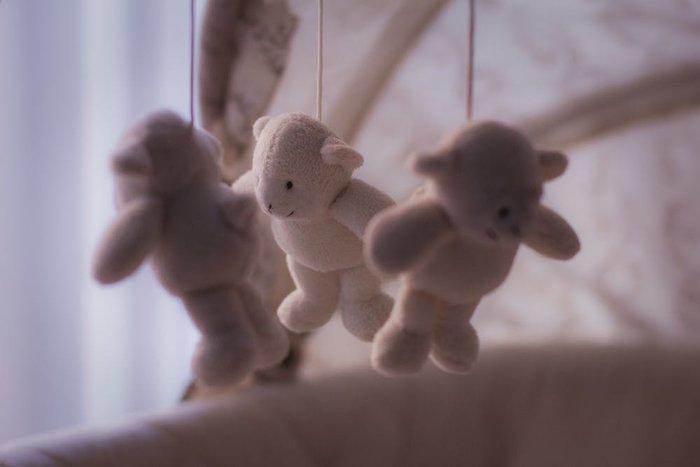 handingn teddy bears baby crib toys closeup shot