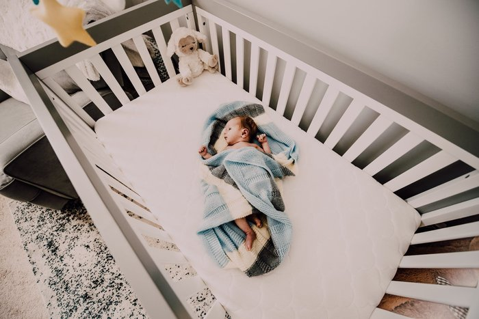 sleeping baby in a crib with toys